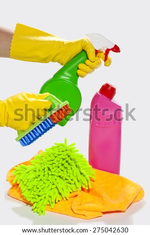 Yellow rubber gloved hand with cleaning supplies ready to cleaning - stock photo