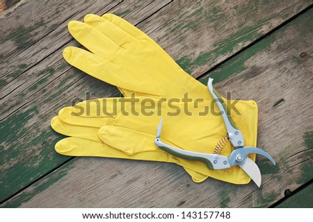 Yellow rubber gloves and garden pruner on wooden background. Closeup. - stock photo