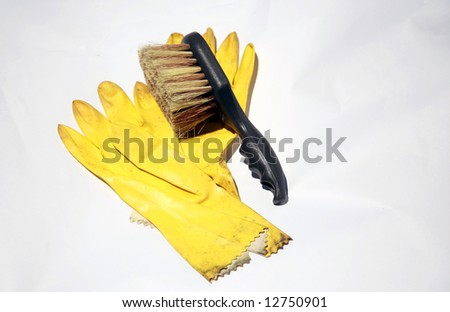 yellow rubber gloves and scrub brush on white, representing the cleaning service industry and other concepts - stock photo