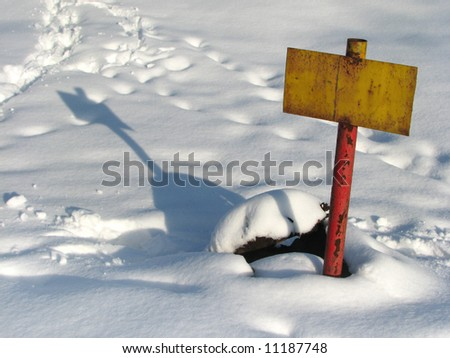 yellow rusty tablet with shadow on snow