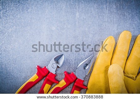 Yellow safety gloves metal pliers wire-cutter electricity concept. - stock photo