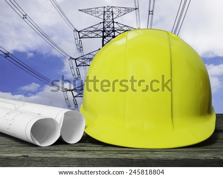 yellow safety hat on wood table over blurred construction site  - stock photo