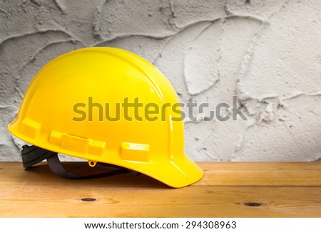 Yellow Safety Helmet on Wooden Floor with Cement Wall Background , color pop tone