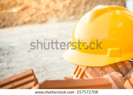 Yellow safety helmet or hard hat in construction site - stock photo