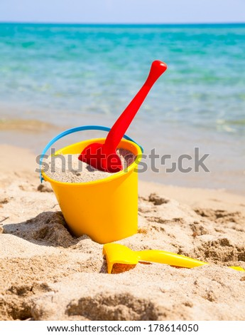 Yellow sand pail and shovel on a beach - stock photo