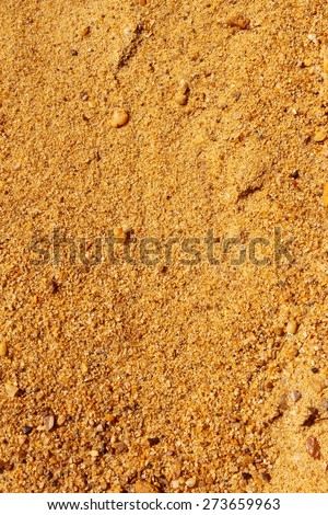 Yellow sand with small colored stones as a texture