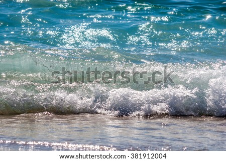Yellow sandy beach and blue sea with waves and seafoam. Background image for travel, summer vacation, and recreation. Vivid photo of tropical paradise. - stock photo