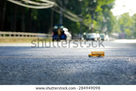 Yellow school bus toy model on street.Shallow depth of field composition and  afternoon scene. - stock photo