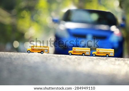 Yellow school buses toy model the road crossing.Shallow depth of field composition and  afternoon scene. - stock photo