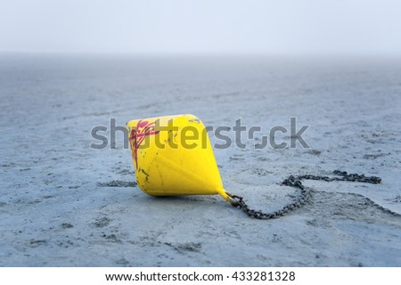 Yellow sea buoy thrown on the coast. In the shallows at low tide. - stock photo