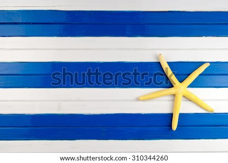 Yellow sea star on a colored wooden background. - stock photo