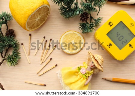 Yellow set of lemon, clock, pencil, small toy doll and matchsticks surrounded by green pine tree branches. - stock photo