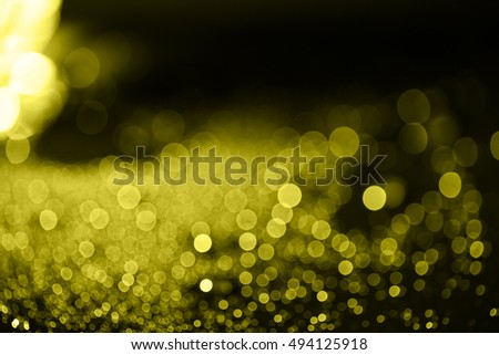 yellow shiny bokeh from water drops on black background