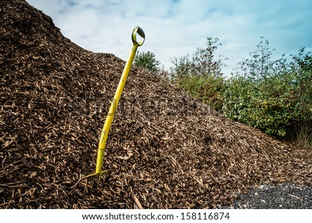 Yellow shovel in a big pile of mulch - stock photo