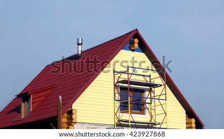 Yellow siding mounting on second floor country house made from wooden logs