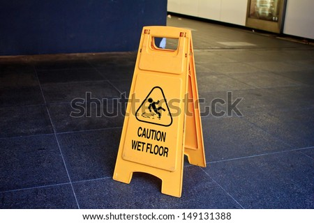 Yellow sign that alerts for wet floor.  - stock photo