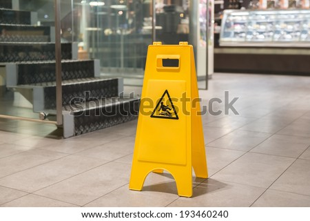Yellow sign that alerts for wet floor - stock photo