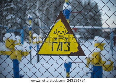 Yellow sign with skull and bones gas underground storage, refinery factory Part of snowy yellow blue pipe with valve Metal rusty sign  Outdoor on winter forest background  - stock photo