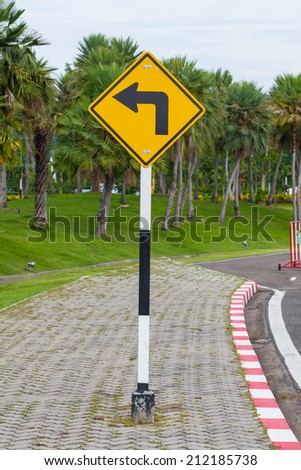 Yellow signs to turn left. Mounted on a sidewalk in the park. - stock photo