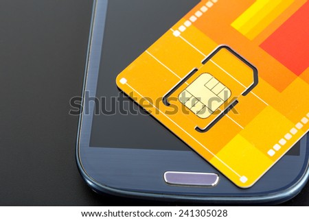 Yellow sim card on the phone - stock photo