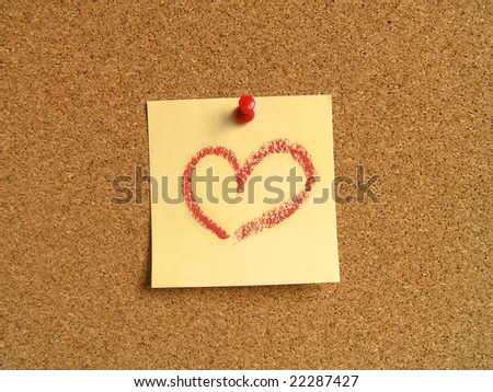 Yellow small sticky note on an office cork bulletin board. The heart painted with a lipstick