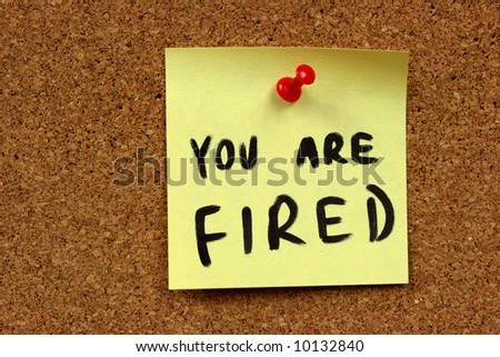 Yellow small sticky note on an office cork bulletin board. You are fired - unemployment and problems at job.