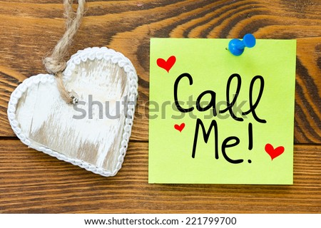 Yellow small sticky note on an wooden table with biscuit heart cookie . Call me! - stock photo