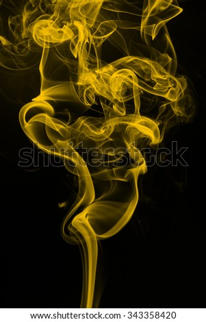 Yellow smoke abstract on black background - stock photo