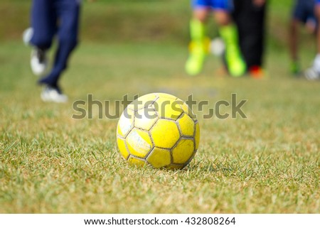 Yellow soccer ball on the grass and training children