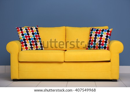 Yellow sofa and multicoloured pillows on a blue wall background - stock photo