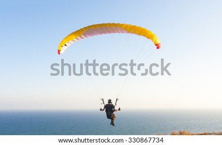 Yellow Sppeedflyer flying over blue sea during sunset - stock photo