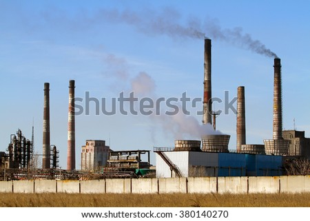 Yellow steppe and factory with smoking chimneys against the blue sky. The juxtaposition of industry and nature.