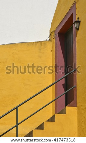 Yellow steps leading up to red doorway in Funchal, Madeira, Portugal - stock photo
