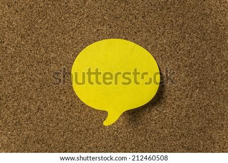 Yellow sticker with shape of speech bubble on cork board - stock photo