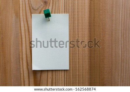yellow sticky note on a wooden background - stock photo