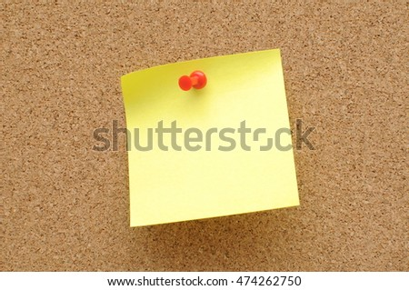 yellow sticky notes with push pin on cork broad