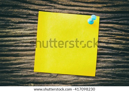 yellow sticky paper note holding by pin on the old wooden background - stock photo