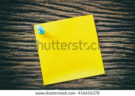 yellow sticky paper note holding by pin on the old wooden background with vintage scene.The yellow note paper with the blue pin at the vintage wooden background.Close-up yellow note with the blue pin. - stock photo