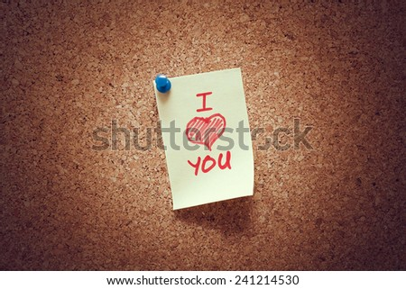 yellow sticky reminder note with i love you message and heart illustration on corkboard.  - stock photo