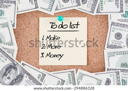 Yellow sticky reminder with TO DO LIST MAKE MORE MONEY message on corkboard with border made of 100 US dollars - stock photo
