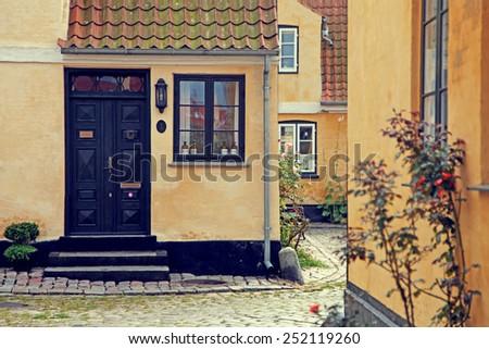 Yellow street of houses in Denmark - stock photo