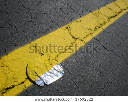Yellow stripe in parking space on top of beer can. They did not remove it. Amazing!!! - stock photo