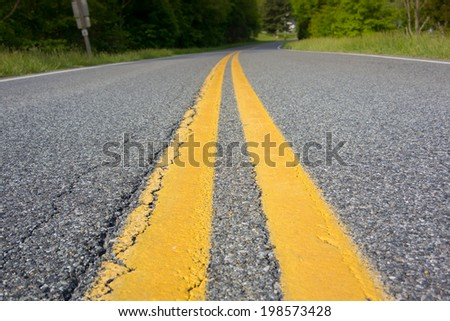 Yellow stripes mark the center of the road in rural Virginia - stock photo