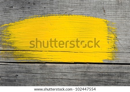 yellow stroke of the paint brush on wooden background - stock photo