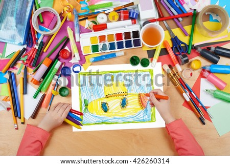 yellow submarine underwater child drawing, top view hands with pencil painting picture on paper, artwork workplace - stock photo