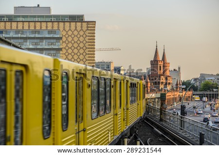 Yellow Subway train on trail to the historical bridge (Oberbaumbruecke) in Berlin, Germany,  Europe - stock photo