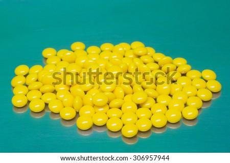 yellow sugar coated tablets on green metal background