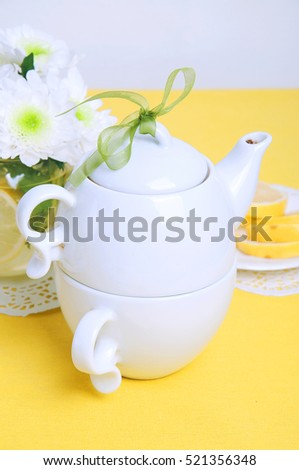 Yellow summer table setting with white teapot and chrysanthemum flowers in a glass vase