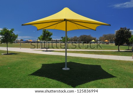 Yellow sun shade umbrella on the Gold Coast - stock photo