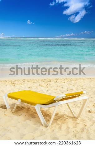 Yellow sunbed on exotic Caribbean beach
